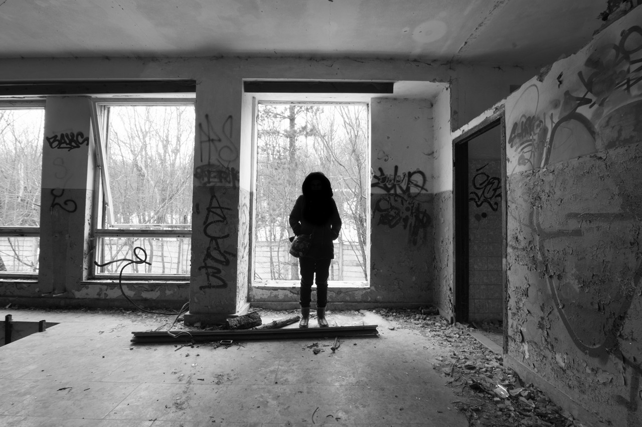 Girl silhouette at abandoned building