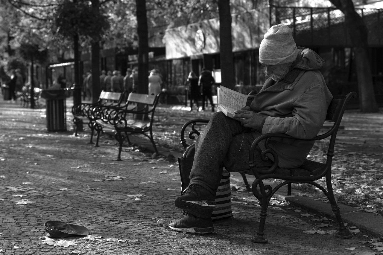 Homeless Man Reading Book & Smooking on the Street Bench